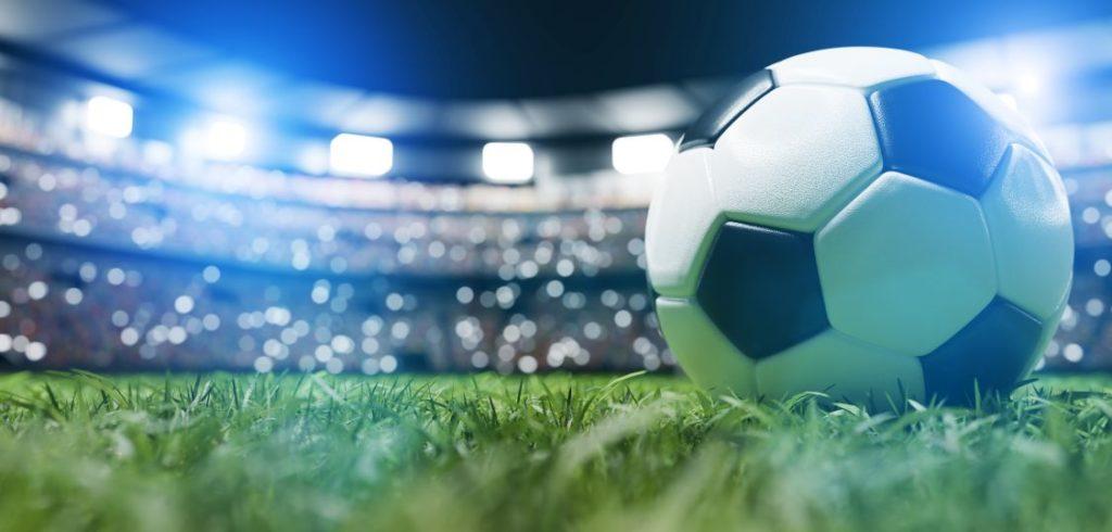 Football soccer ball on grass field on stadium, evening match.